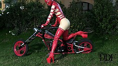 Freaky babe in red latex bondage gear fucks herself on a bike