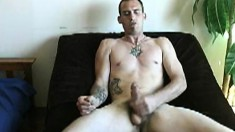 Tattooed young dude shows off his body while stroking his piston